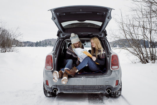 Female friends reading map while sitting in car trunk during winter