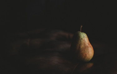 Close-up of pear on table against black background