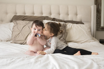 Girl kissing her brother while sitting on bed at home
