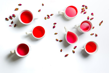Rose tea in cups on white background