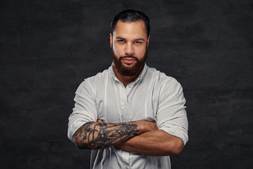 Portrait of a handsome African-American tattooed man with stylish hair and beard, stands with crossed arms.