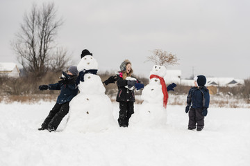 Siblings playing with snowman during winter