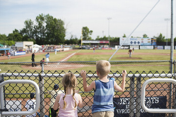 Rear view of siblings watching baseball match through fence at stadium