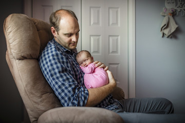 Father carrying newborn daughter while sitting on armchair at home