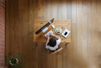 Overhead view of businesswoman using desktop computer at table on hardwood floor in home