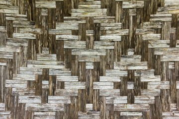 Geometric figure shapes brown wall made of bamboo. Wicker background texture