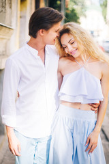 Happy newlywed couple on a relaxing walk in sunny Paris during summer honeymoon, smiling man hugging beautiful woman in hipster blue top and skirt outdoors
