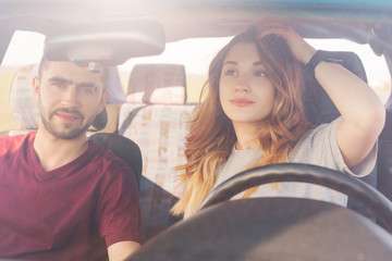 Beautiful young female driver looks in mirror of car, sits next to her husband or boyfriend, have journey together, drive on country road. Family couple choose new vehicle in automobile dealership