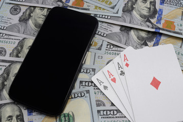 virtual casinos, real money. cell phone, dollar and playing cards