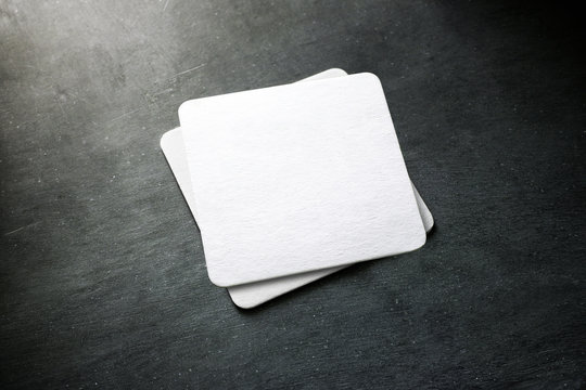 Blank white beer coaster stack mockup, top view, lying on the textured background. Squared clear can mat design mock up isolated. Quadrate cup rug display