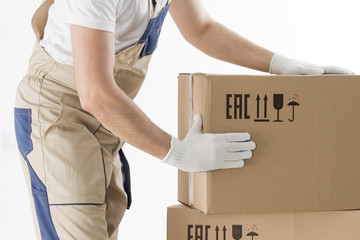 relocation services concept. Mover's hands In uniform carrying cardboard Box. Loader puts cardboard boxes isolated on white background. Worker mover unloading paper box. Delivery man