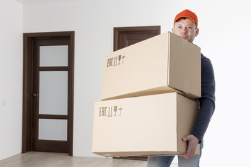 Moving service relocation. Mover holding two cardboard box in apartment's room. loader is transporting things to apartment. man from delivery service brought parcel