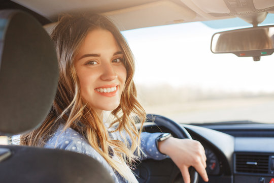 Close up portrait of pleasant looking female with glad positive expression, being satisfied with unforgettable journey by car, sits on driver`s seat, enjoys music. People, driving, transport concept