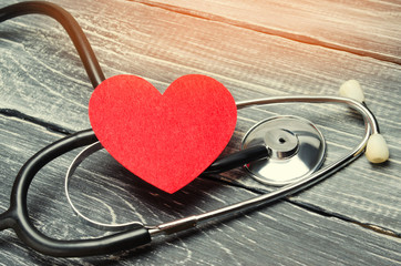 the concept of family medicine and insurance. stethoscope and heart on a wooden background