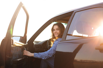 Positive woman sits in black car, looks with happy smile on face, tries to close door, ready for long trip, enjoys driving. Satisfied female driver glad to buy new transport. People, road, journey