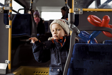 Cute boy with balloons wearing warm clothing while pointing in bus