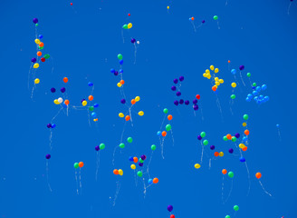 Multicolored balls, filled with helium, fly in the blue sky.