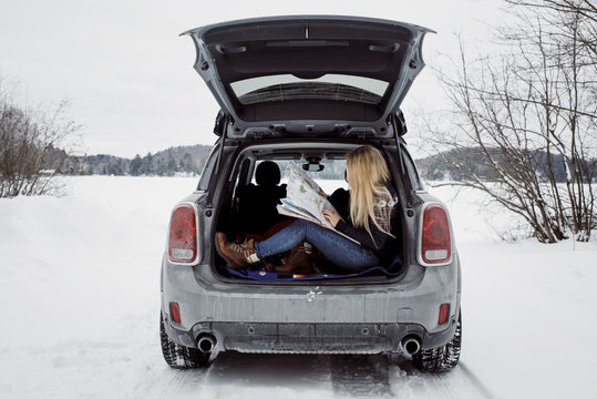 Side view of woman reading map while sitting in car trunk during winter