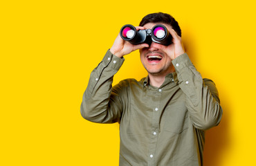 Young man looking for something with binoculars on yellow background