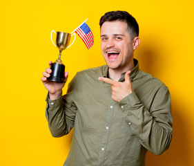 Young man holding an American flag and golden cup on blue background