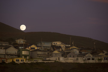 Full moon rising above a small beach town at the base of a hill at dusk.