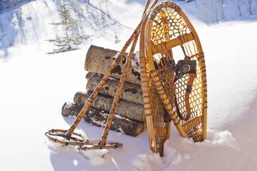 Wooden snow shoes and snow poles leaning against a stack of cut firewood in the snow.