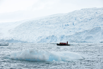 Group of tourists sightseeing on a boat surrounded by icebergs.
