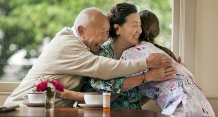 Happy senior couple hugging female nurse at home