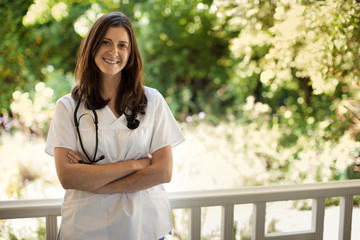 Portrait of young female nurse standing on the verandah of someone's home.
