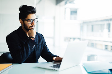 Indian man working on laptop in modern office. Young business man in glasses work on laptop