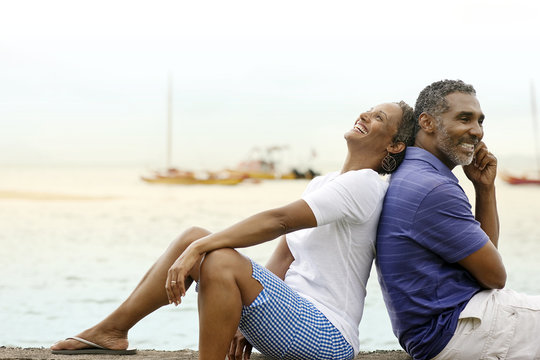 Happy mature couple sitting back to back by the beach.