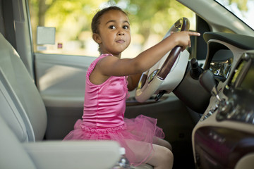 Young girl dressed as a ballerina pretending to drive a car.