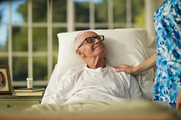 Smiling senior man being comforted by a female nurse while lying in bed.