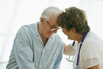 Happy senior man sharing a laugh with a female nurse.