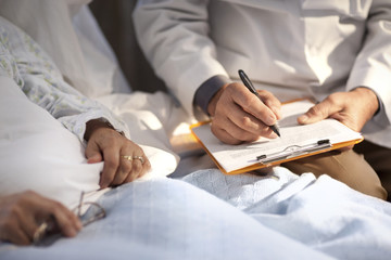 Doctor taking notes while sitting with a patient in hospital.