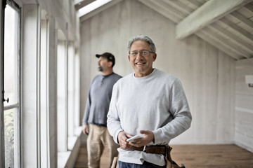 Builder looking at camera while client admires view in background.