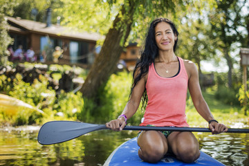 Mid adult woman prepares for paddleboarding.