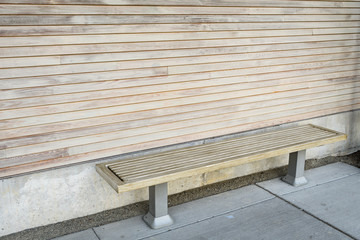 A wood bench against a textured wood wall on a concrete patio, a place to rest