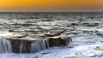 Sunrise Seascape with Cascades over the Rock Ledge