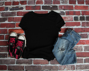 Mockup blank black t shirt with jeans and shoes on brick background