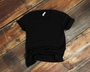 Mockup of blank black tshirt on rustic wood background