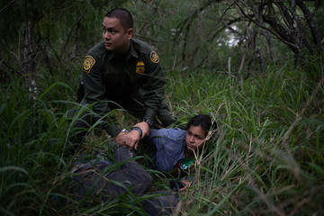 A border patrol agent apprehends a woman after she was caught illegally crossing into the U.S. border from Mexico near McAllen, Texas, U.S.