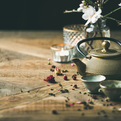 Traditional Asian tea ceremony arrangement. Golden iron teapot, cups, candles and almond blossom flowers over vintage wooden table background, copy space, selective focus, square crop