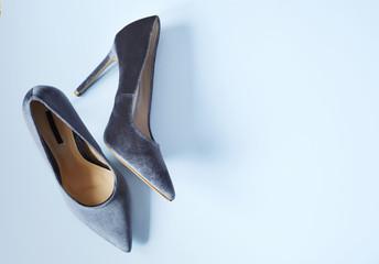 Velvet grey women high heel shoes on light blue background. Velvet pumps