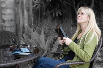 Middle aged woman praying outside with Bible