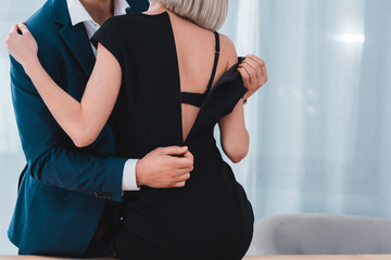 cropped shot of businessman taking off black dress from young female colleague in office