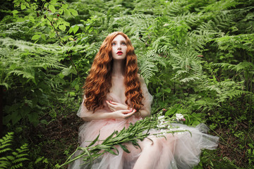 Beautiful pre-raphaelite girl with curly red hair with a flying tulle dress on the background of a green fern