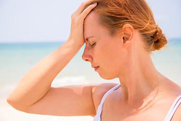 Headache woman on sunny beach. Woman with sunstroke. Hot sun danger. Health problem on holiday.