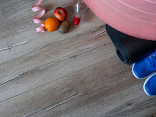 Fitness accessories. Sports shoes. Women items for sports life. Measuring tape, centimeter. The concept of sport for weight loss. Bottle of water. Fruits. Flatlay.