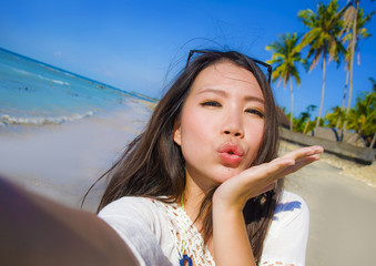 self portrait of gorgeous beautiful and happy Asian Korean or Chinese woman 20s taking selfie photo sending kiss with mobile phone camera